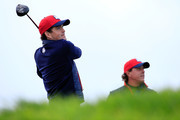 Keegan Bradley of the United States tees off watched by Phil Mickelson during practice ahead of the 2014 Ryder Cup on the PGA Centenary course at the Gleneagles Hotel on September 25, 2014 in Auchterarder, Scotland.