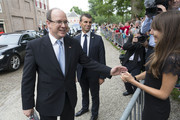 Prince Albert II of Monaco (L) receives a gift from a Belgian TV reporter after leaving the Loo Royal Palace on June 3, 2014 in Apeldoorn, Netherlands.