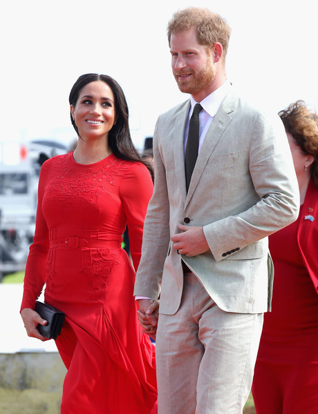 The Duke And Duchess Of Sussex Visit Tonga - Day 1 [red,suit,formal wear,flooring,fashion,outerwear,carpet,event,smile,gown,harry,tonga,duke and duchess of sussex,duchess,sussex,cities,fuaamotu airport,duke of sussex,visit,tour]