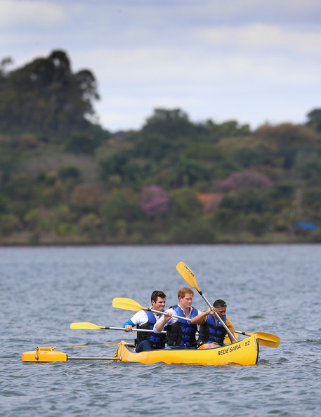 Prince Harry canoes with patient Israel Lima (front) and an instructor from the Rede Sarah Hospital for Nerological Rehabilitation injuries as he takes part in a canoe therapy session on Lake Paranoa on June 23, 2014 in Brasilia, Brazil.  Prince Harry is on a four day tour in Brazil that will be followed by two days in Chile.