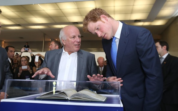 Football Association Chairman Greg Dyke shows Prince Harry a copy of the First Rules of Football during a visit to Minas Tenis Clube on the second day of his tour of Brazil on June 24, 2014 in Belo Horizonte, Brazil. Prince Harry is on a four day tour of Brazil that will be followed by two days in Chile.