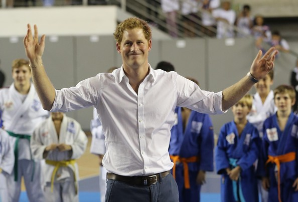 Prince Harry gestures as plays football with young school children during a visit to Minas Tenis Clube on the second day of his tour of Brazil on June 24, 2014 in Belo Horizonte, Brazil. Prince Harry is on a four day tour of Brazil that will be followed by two days in Chile.