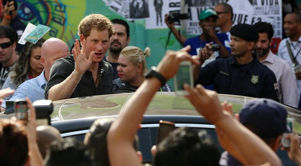 Prince Harry waves to members of the public as he visits the Open Arms project which helps reduce crime and drug abuse in 'Cracolandia', an extremely deprived area of Sao Paulo with a high concentration of crack addicts on June 26, 2014 in Sao Paulo Brazil. Crack in Sao Paulo costs just 80 UK pence for a rock of the drug. Prince Harry is on a four day tour of Brazil that will be followed by two days in Chile.