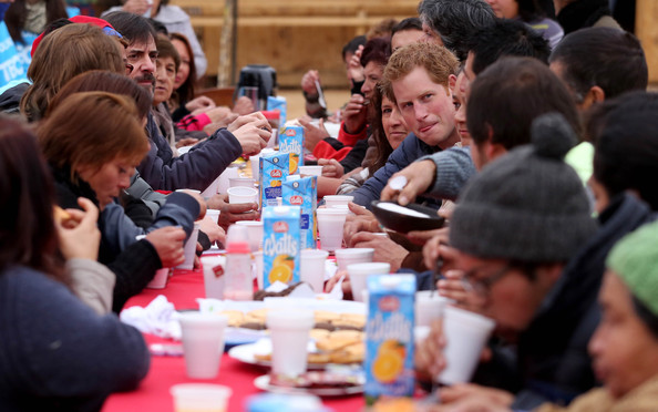 Prince Harry has tea with the residents as he is shown the devastation left by the Valparaiso fire that burnt down many homes in the poorest area of the town on June 28, 2014 in Valpariso, Chile. Firefighters from Valpariso were involved in dealing with the devastating forest fires that hit the area in April. Prince Harry is on a three day tour of Chile after visiting Brazil.