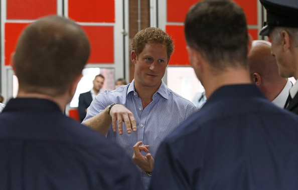 Prince Harry gestures as he chats with firefighters during his visit to Salford Fire Station on October 20, 2014 in Manchester, England.