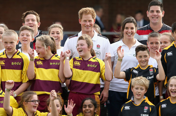 Prince Harry, Patron of England Rugby's All Schools Programme poses for a photo with schoolchildren and England women's rugby player Sarah Hunter (2nd R) after a teacher training session at Eccles RFC on October 20, 2014 in Manchester, England.