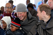 Prince Harry and Prince William clap as Prince Harry holds a young boy during a visit to a child education centre on June 16, 2010 in Semonkong, Lesotho. The two Princes are on a joint trip to Africa which takes in Botswana, Lesotho and finally South Africa. During that time they will visit a number of projects supported by their respective charities Sentebale (Prince Harry) and Tusk Trust (Prince William). The trip will culminate with the brothers watching the England vs Algeria World Cup match in Cape Town.