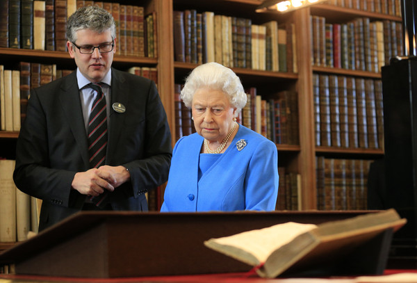 Queen Elizabeth II is shown items from the George III Collection pertaining to science and the Arts, including the 1765 Eardley Norton clock (R) by Royal Librarian Oliver Urquhart Irvine (L) while attending the launch of the George III Project at an event held in the Royal Library in Windsor Castle on April 1, 2015 in Windsor, England.