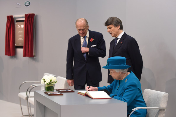 Queen Elizabeth II signs the visitor book alongside Prince Philip, Duke of Edinburgh and Jaguar Land Rover Chief Executive Dr Ralf Speth after officially opening the new Jaguar Land Rover Engine Manufacturing Centre in Wolverhampton on October 30, 2014 in Wolverhampton.