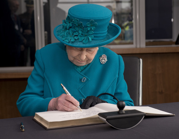 Queen Elizabeth II signs the visitors book during an official visit to International Security Printers to view their work on specialist postage stamps on October 30, 2014 in Wolverhampton, England.