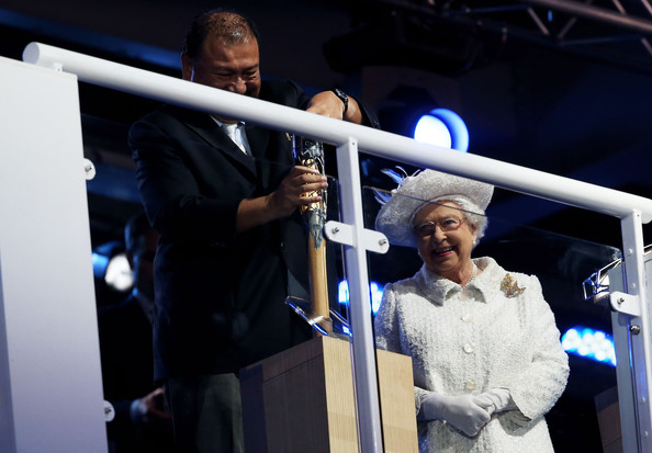 Queen Elizabeth II Prince Imran the CGF President attempts to retrieve the message from the baton as he presents it to Queen Elizabeth II, Patron of the CGF during the Opening Ceremony for the Glasgow 2014 Commonwealth Games at Celtic Park on July 23, 2014 in Glasgow, Scotland.