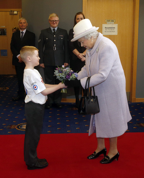 Queen Elizabeth II is presented with a posy of flowers by eight-year-old Lennon Gallagher during a visit to RAF Lossiemouth on her 67th wedding anniversary on November 20, 2014 in Lossiemouth, Scotland. It was the Queen's first visit to the base since 2003.