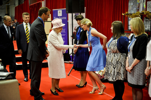 Trainee design manager Kerry Deller curtseys as she meets Queen Elizabeth II during a visit to International Greetings UK Ltd at the Penallta Industrial Estate in Ystrad Mynach during her visit to south west Wales on April 30, 2014 in Ystrad Mynach, Wales.