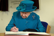 Queen Elizabeth II signs the visitors book as she visits The Norfolk Hospice at Hillington on February 4, 2016 near King's Lynn, England. The Queen met patients, trustees, volunteers and medical professionals working at the hospice, which has been serving its local community close to her Sandringham Estate for over 30 years.