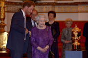 Queen Elizabeth II and Prince Harry looks at the Webb Ellis Cup on a plinth during a reception to mark the Rugby World Cup 2015 at Buckingham Palace on October 12, 2015 in London, United Kingdom.