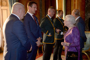 Queen Elizabeth II meets Wales' Rugby Union Captain Sam Warburton (second left) and Wales' head coach Warren Gatland (left) at a reception at Buckingham Palace on October 12, 2015 in London, United Kingdom.