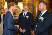 Prince Harry (left) speaks to Australian Rugby Union player Stephen Moore and Australia head coach Michael Cheika (right) at a Rugby World Cup reception at Buckingham Palace on October 12, 2015 in London, United Kingdom.