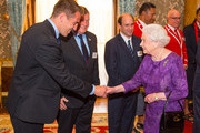 Queen Elizabeth II meets (left to right) USA's Rugby Union player Chris Wyles, USA Rugby Union Team Manager Tristan Lewis and Uruguay's Sebastian Pineyrua at a Rugby World Cup reception at Buckingham Palace on October 12, 2015 in London, United Kingdom.