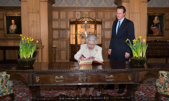 Queen Elizabeth II signs a visitors book at Chequers watched by Prime Minister David Cameron where she and Prince Philip, Duke of Edinburgh had lunch with the PM and his wife Samantha, on February 28, 2014 near Aylesbury, England. It is the first time the Queen has visited the PM's official country residence in Buckinghamshire since 1996.