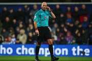 Referee Mike Dean looks on during the Barclays Premier League match between Queens Park Rangers and Manchester City at Loftus Road on November 8, 2014 in London, England.