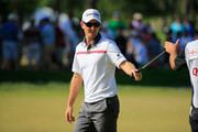 Justin Rose of England hands his putter to his caddie Mark Fulcher (R) after making his putt on the 14th hole during the final round of the Quicken Loans National at Congressional Country Club on June 29, 2014 in Bethesda, Maryland.