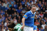 David Wier (R) and Sasa Papac (hidden) of Rangers tackle Georgios Samaras of Celtic during the Clydesdale Bank Premier League match between Rangers and Celtic at Ibrox Stadium salutes his supporters  on April 24, 2011 in Glasgow, Scotland.