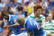 Maurice Edu (L) and Madjid Bougherra (C) of Rangers tackle Ki Sung- Yueng of Celtic during the Clydesdale Bank Premier League match between Rangers and Celtic at Ibrox Stadium on April 24, 2011 in Glasgow, Scotland.