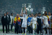 Gareth Bale of Real Madrid CF holds the UEFA Champions cup surrounded by teammates and head coach Carlo Ancelotti (L) during the Real Madrid celebration the day after winning the UEFA Champions League Final at Santiago Bernabeu stadium on May 25, 2014 in Madrid, Spain.