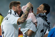 Sergio Ramos (L) of Real Madrid CF is shown with teammate Angel Di Maria and his daughter during the Real Madrid celebration the day after winning the UEFA Champions League Final at Santiago Bernabeu stadium on May 25, 2014 in Madrid, Spain.