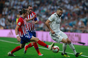 Karim Benzema (R) of Real Madrid CF competes for the ball with Filipe Luis (L) of Atletico de Madrid and his teammate Diego Godin (2ndL) during the La Liga match between Real Madrid CF and  Club Atletico de Madrid at Estadio Santiago Bernabeu on September 29, 2018 in Madrid, Spain.