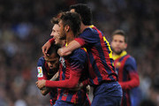 Lionel Messi of Barcelona celebrates scoring his team's third goal with Neymar and Daniel Alves of Barcelona during the La Liga match between Real Madrid CF and FC Barcelona at the Bernabeu on March 23, 2014 in Madrid, Spain.