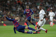 Gerard Pique of FC Barcelona tackles Vinicius Junior of Real Madrid during the Liga match between Real Madrid CF and FC Barcelona at Estadio Santiago Bernabeu on March 01, 2020 in Madrid, Spain.