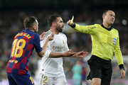 Daniel Carvajal of Real Madrid and Jordi Alba of FC Barcelona are both showed a yellow card by .referee Antonio Mateu Lahoz during the Liga match between Real Madrid CF and FC Barcelona at Estadio Santiago Bernabeu on March 01, 2020 in Madrid, Spain.