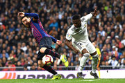 Lionel Messi of Barcelona and Vinicius Junior of Real Madrid in action during the La Liga match between Real Madrid CF and FC Barcelona at Estadio Santiago Bernabeu on March 02, 2019 in Madrid, Spain.