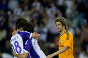 Fabio Coentrao (R) of Real Madrid CF watches Alvaro Rubio (L) of Real Valladolid CF embrace his team-mate Marc Valiente (2nd R) to cerlebrate their tieafter the La Liga match between Real Valladolid CF and Real Madrid CF at Estadio Jose Zorilla on May 7, 2014 in Valladolid, Spain.