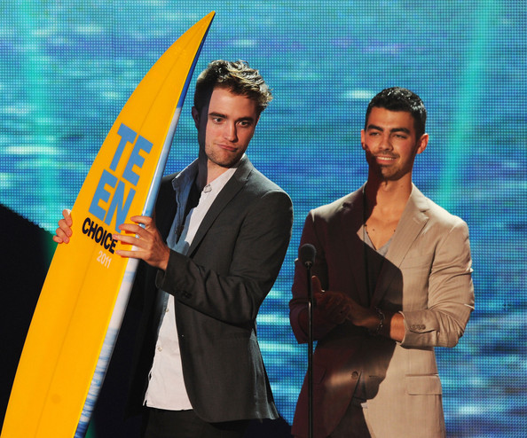 Robert Pattinson Actor Robert Pattinson (L) and singer Joe Jonas onstage during the 2011 Teen Choice Awards held at the Gibson Amphitheatre on August 7, 2011 in Universal City, California.