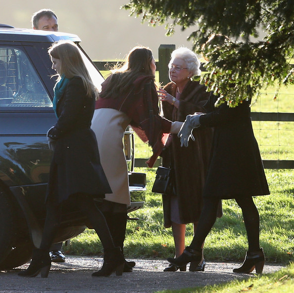 Queen Elizabeth II (2ndR), embraces Catherine, Duchess of Cambridge (2ndL) as they arrive at the Christmas Day service at Sandringham on December 25, 2013 in King's Lynn, England.