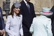 Catherine, Duchess of Sussex curtsies as Queen Elizabeth II arrives for the Easter Sunday service at St George's Chapel on April 21, 2019 in Windsor, England.