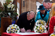 Prince Philip, Duke of Edinburgh signs the guest book as Queen Elizabeth II looks on during the Royal Maundy service at Leicester Cathedral on April 13, 2017 in Leicester, England. The Queen & Duke of Edinburgh travelled by car from Leicester station along Humberstone Gate, High Street and Jubilee Square.