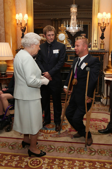 Queen Elizabeth II meets para-equestrian ridere Lee Pearson during a reception for the Team GB Olympic and Paralympic medalists at Buckingham Palace on October 23, 2012 in London, England.