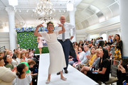 Zoey Nieves and Brian Cashman walk the runway as Runway Heroes Walk With The Yankees At Kleinfeld on June 18, 2019 in New York City.