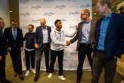 Seattle Seahawks quarterback Russell Wilson shakes hands with Nordstrom co-president Pete Nordstrom with Erik Nordstrom standing close by at Nordstrom on February 29, 2016 in Seattle, Washington.