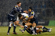 Matt Banahan of Bath is tackled by Nick MacLeod (L), Sam Tuitupou (C) and Daniel Braid of Sale during the Aviva Premiership match between Sale Sharks and Bath Rugby at the Salford City Stadium on March 22, 2013 in Salford, England.