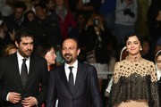 """(FromL) Iranian director of photography Hossein Jafarian, Iranian director Asghar Farhadi and Iranian actress Taraneh Alidoosti pose as they arrive on May 21, 2016 for the screening of the film """"The Salesman (Forushande)"""" at the 69th Cannes Film Festival in Cannes, southern France.  / AFP / ALBERTO PIZZOLI"""