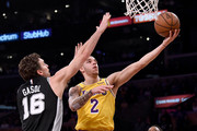 Lonzo Ball #2 of the Los Angeles Lakers scores on a layup past Pau Gasol #16 and DeMar DeRozan #10 of the San Antonio Spurs during the first half at Staples Center on October 22, 2018 in Los Angeles, California.