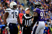 Referee Walt Anderson separates tackle D.J. Fluker #76 of the San Diego Chargers and outside linebacker Courtney Upshaw #91 of the Baltimore Ravens in the first quarter of a game at M&T Bank Stadium on November 30, 2014 in Baltimore, Maryland.