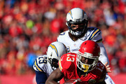 Running back De'Anthony Thomas #13 of the Kansas City Chiefs makes a catch as cornerback Shareece Wright #29 and free safety Eric Weddle #32 of the San Diego Chargers defend during the game at Arrowhead Stadium on December 28, 2014 in Kansas City, Missouri.
