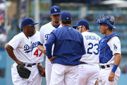 Pitching coach Rick Honeycutt visits the mound to talk to pitcher Carlos Frias #77 as Jimmy Rollins #11, Adrian Gonzalez #23 and catcher Austin Barnes #65 look on in the second inning during the MLB game against the San Diego Padres at Dodger Stadium on May 24, 2015 in Los Angeles, California.