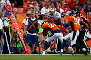 Cornerback Aqib Talib #21 of the Denver Broncos tackles running back Reggie Bush #23 of the San Francisco 49ers during preseason action at Sports Authority Field at Mile High on August 29, 2015 in Denver, Colorado. The Broncos defeated the 49ers 19-12.