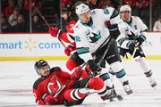 Marcus Johansson #90 of the New Jersey Devils is dumped by Kevin Labanc #62 of the San Jose Sharks on the opening faceoff at the Prudential Center on October 14, 2018 in Newark, New Jersey.
